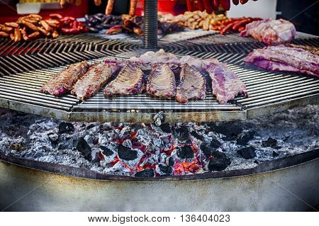 A huge circular grill loaded with assorted ribs chorizos chicken and others