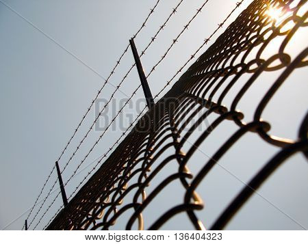 Chain link fence and  barbed wire with pale blue sky and sun flare.