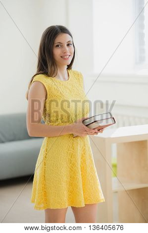Smart beautiful Student girl wearing yellow dress holding book in school class or library.