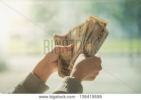 Woman's hand counting money Japanese currency note Japanese yen