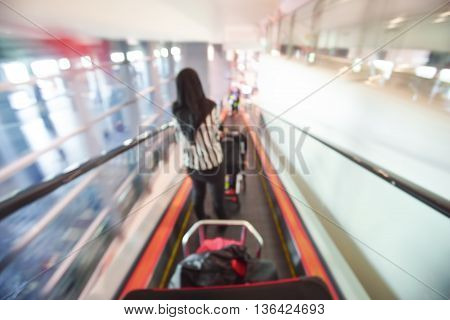 Blur image of people walking down the escalator at airport