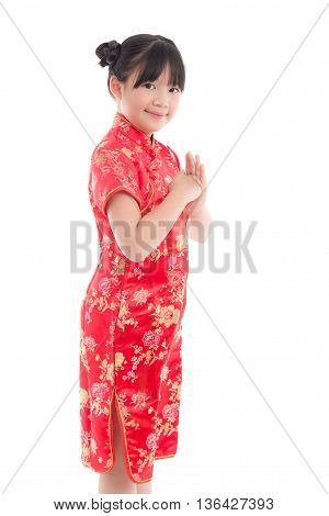 Beautiful asian girl wishing you a happy Chinese New Year with traditional Cheongsam standing isolated on white background.