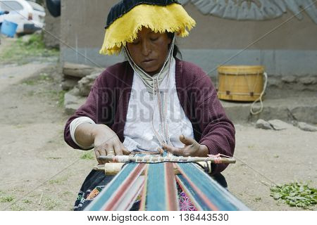 October 22 2012 - Paru Paru, Peru: Peruvian woman weaving cloth on a hand loom.