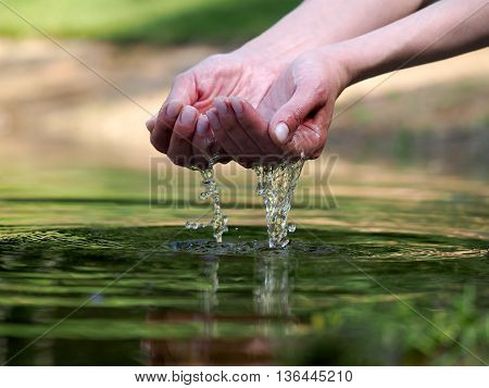 Women's hands are holding in your hands the water