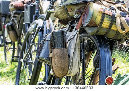 Close up photo of old military bicycle with kitbag and equipments. Backpack and containers for food and drink. Vintage scene. Retro transport. Equipment of german soldier in World War II.