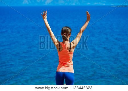 Happy woman enjoying freedom on travel in Crete coast, Greece. Female on summer or spring leisure vacation raising arms to sky towards the sea