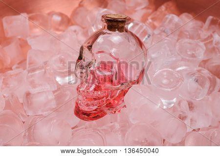 human crystal head skull pink bottle on ice close up