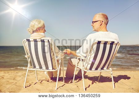 family, age, travel, tourism and people concept - happy senior couple resting in folding chairs on summer beach from back
