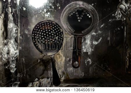 two cocktail strainers on a ice background