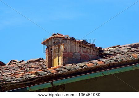 dormer brick and old wooden door on traditional roof with roof tiles