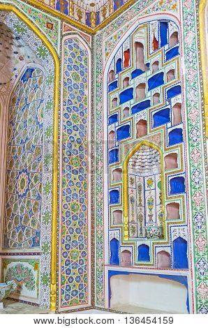 BUKHARA UZBEKISTAN - APRIL 29 2015: The shelves for the porcelain presented to Emir of Bukhara carved into the wall and painted into the different colors Museum of Costume of Sitorai Mokhi-Khosa Complex on April 29 in Bukhara.