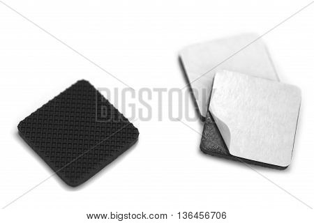 Anti scratch and slip rubbers with builtin adhesive over white background with one piece showing adhesive by peeling thin white sheet