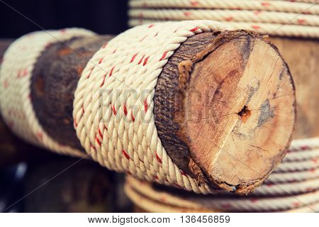 building, construction and eco concept - wooden beam wrapped with rope