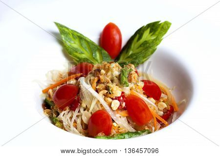 som tum thai served in white plateThai papaya spicy salad or know as Som Tum.