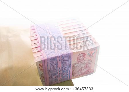 10 packs of 100 of new hundredth baht notes within brown envelope worth 100000 baht over white background