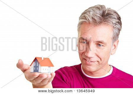 Senior Man Looking At Miniature House