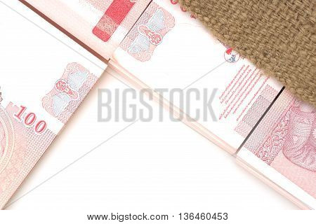 Pack of 100 bank notes of 100 Thai baht inside agriculture sack over white table background