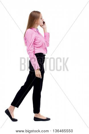 side view of a woman walking with a mobile phone. back view ofgirl in motion.  backside view of person.  Rear view people collection. Office worker girl in pink shirt talking on the phone to the left.