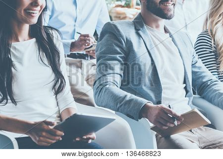 Business conference concept. Close-up of cheerful young business people sitting on conference together and smiling