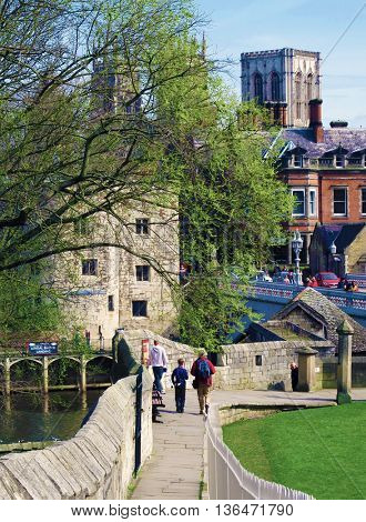 View of tourists walking along York walls with York Minster in far background