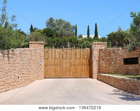 Wooden gate of a mansion with drystone wall and security system.