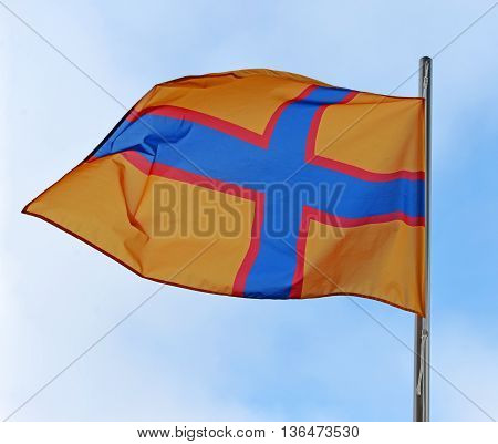 Ingermanland flag waving in the wind against a blue sky with clouds. Ingermanland (Inkeri Ingeri) ethnocultural and historical area in the northwest of Russia.