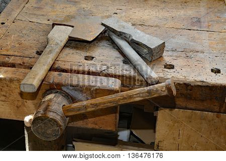 Axe And Big Hammer On The Old Wooden Workbench With A Vise