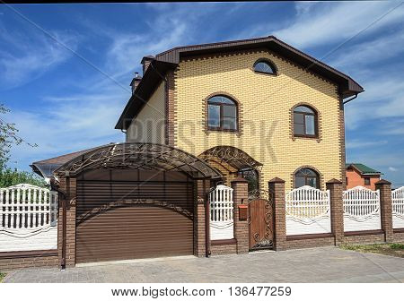 Two-storeyed yellow brick cottage with white concrete fence and metal gate sunny summer day