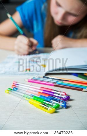 Child painting a coloring book. New stress relieving trend. Concept mindfulness relaxation.