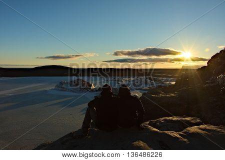 Couple enjoys sunset above glacier in Iceland
