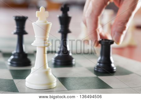 White chess king alone surrounded by the opposite pieces selective focus on white chess king piece male hand touching about to move a chess piece