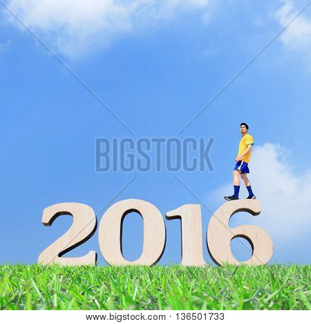 Soccer player man and stand on the 2016 text with blue sky