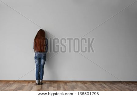 Family problems concept. Punished girl standing near wall