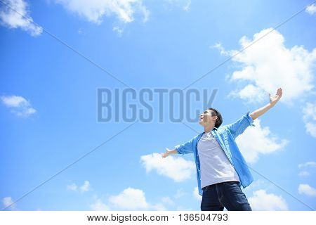 Carefree and free man raised hands and looking to a sky asian