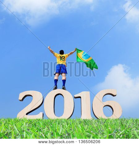 Excited man holding a brazil flag and stand on the 2016 text with blue sky