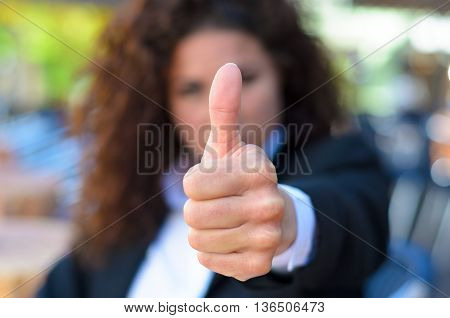 Young woman giving a thumbs up gesture to show her approval endorsement support good excellent choice or success or to indicate a yes vote focus to her hand