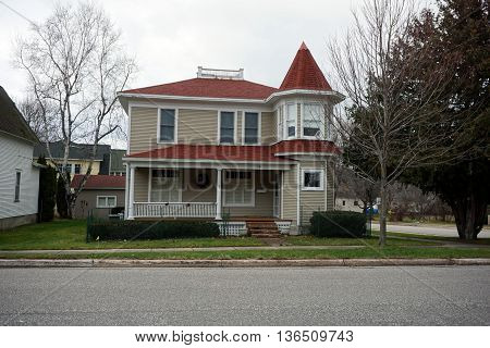 HARBOR SPRINGS, MICHIGAN / UNITED STATES - DECEMBER 24, 2015: An elegant home with a front porch and a turret near downtown Harbor Springs.