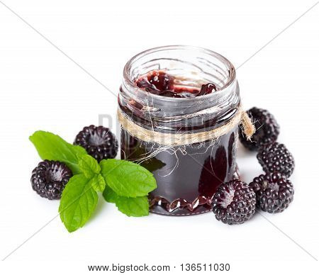 Jam made from black raspberries Cumberland in glass jar and leaves of mint isolated on white background