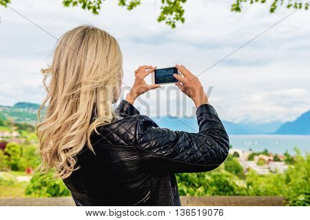 Young blond woman photographing with smart phone beautiful landscape in Lavaux vineyards, Switzerland