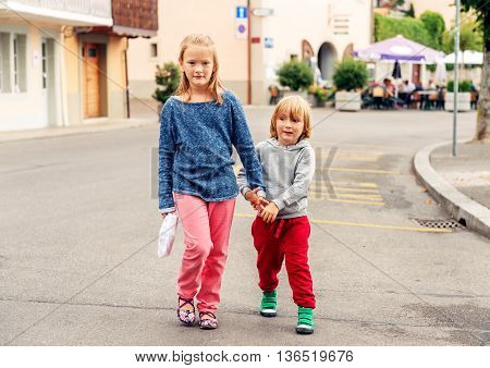 Outdoor portrait of adorable fashion kids walking down the street