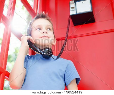 smiling boy stands in a red telephone box. concept of sharing emotions, impressions and feelings. happy child holding a black telephone handset and wait for a phone call in a red telephone booth. old school