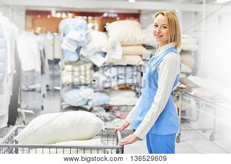 Girl worker holding a Laundry cart with clean pillows at the dry cleaners