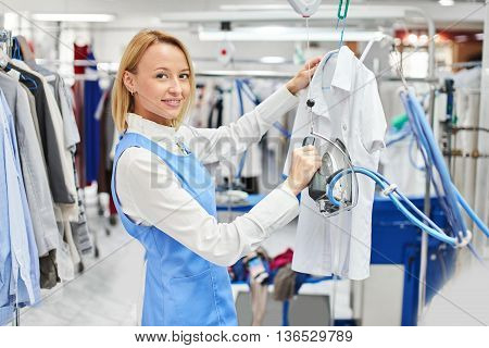 Girl worker Laundry ironed clothes and smiling at the dry cleaners