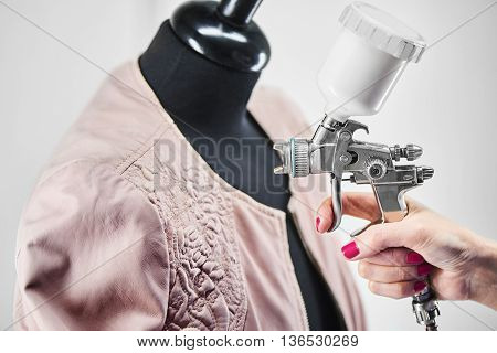 Hands carry out the process of painting a leather jacket on the mannequin
