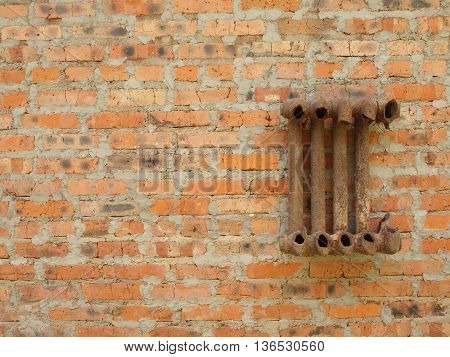 Ruined cast iron radiator for home on a brick wall.