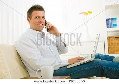 Casual businessman working at home sitting on couch, using laptop computer, talking on mobile phone.