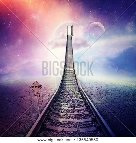 Railroad of opportunity along a cracked desert ground going up as a staircase to a opened door in space road to heaven symbol. Success plan business concept