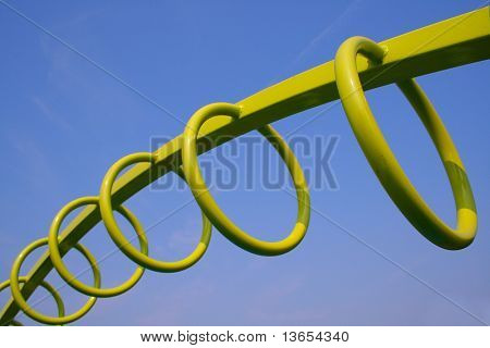 Green Monkey Exercise Hoops from a playground against blue sky