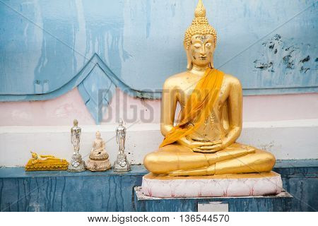 Golden Buddha with yellow fabric and little pieces close against the wall of the temple in Thailand on Koh Samui
