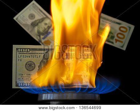 Dollar bill on fire in gas burner flame. Gas burner burning one hundred dollar bill on black background.
